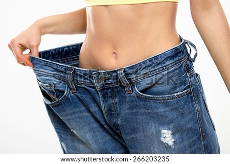 Diet. Beautiful Sporty Woman Showing How Much Weight She Lost. Healthy lifestyles concept - stock photo