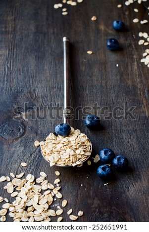 Diet Breakfast. Oats in a vintage metal spoon  and berries on wooden background - health and diet concept. Selective focus. - stock photo