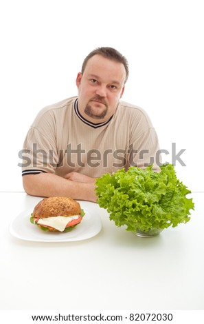 Diet choices concept - man with hamburger and lettuce at the table, isolated - stock photo