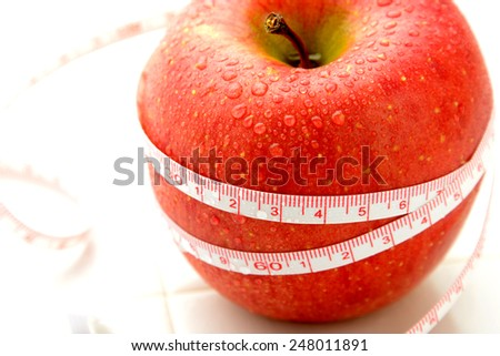 Diet concept, apple and measuring tape - stock photo