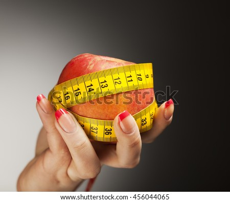 Diet concept: apple with measure tape in woman hand - stock photo