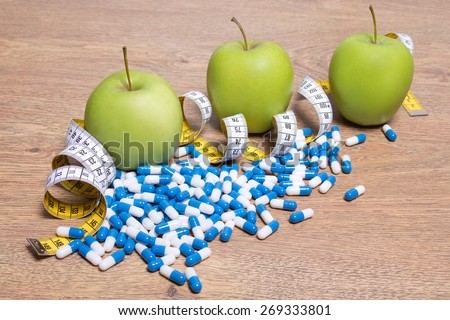 diet concept - apples, pills and measure tape on wooden table - stock photo