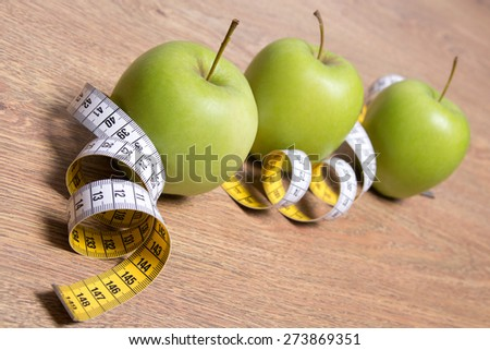 diet concept - close up of green apples and measure tape on wooden table - stock photo