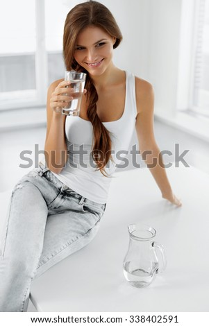 Diet Concept. Close-up Portrait Of Happy Smiling Young Woman Drinking Refreshing Cold Water From Glass In The Morning. Healthy Eating. Dieting Concept. Nutrition. Healthcare And Beauty. - stock photo