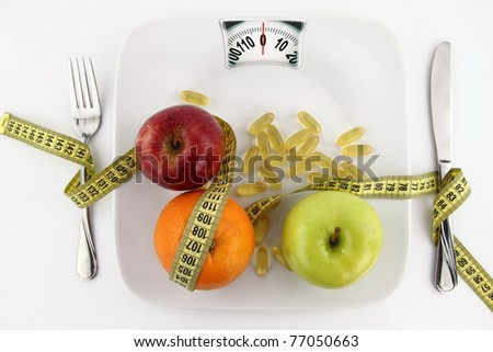 Diet concept. Fruits and vitamins with measuring tape on a plate like weight scale - stock photo