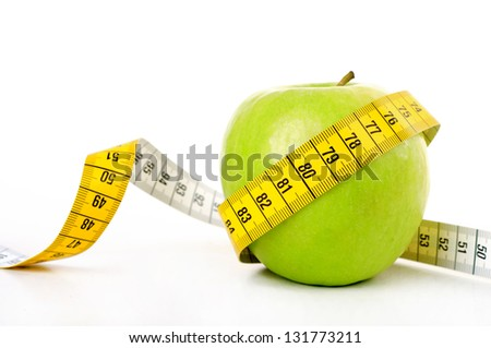 Diet concept, green apple wrapped with measuring tape - stock photo