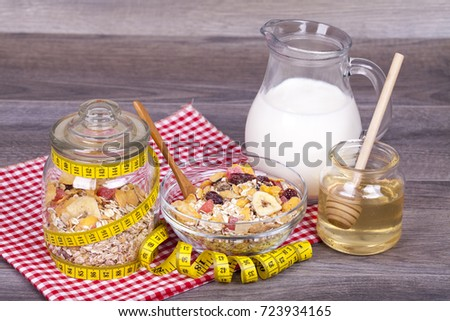 Diet concept .Healthy meal - breakfast. Musli with dried fruit, milk - yogurt and honey on a wooden backgraund. With empty space for your text.