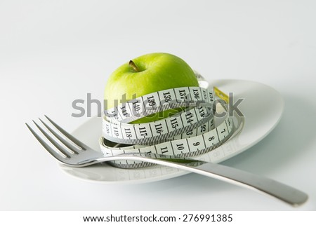 Diet concept illutrated with measuraing tape wrapped on green apple