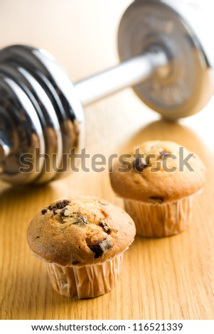 Diet concept. Muffin and dumbbell on background. - stock photo