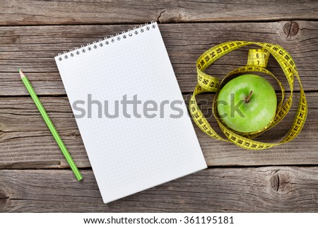 Diet concept. Notepad, tape measure and apple on wooden table. Top view with copy space