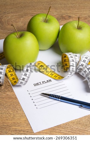 diet concept - paper with diet plan, green apples and measure tape on wooden table - stock photo