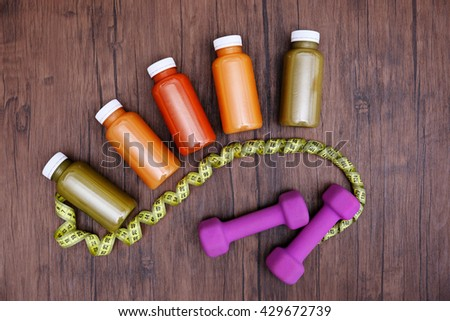 Diet concept: vegetable juices in bottles, dumbbells and measuring tape on wooden background - stock photo