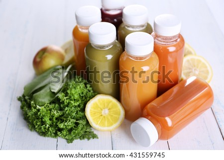 Diet concept: vegetable juices in bottles on wooden background - stock photo