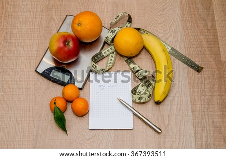 Diet concept with fruit, notebook and measuring tape on wooden table - stock photo