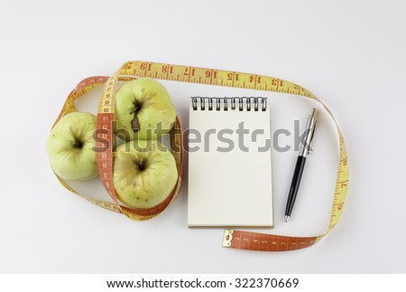 Diet concept with green apple, a notebook, pen and a measuring tape