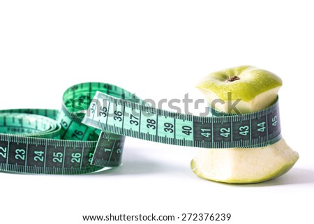 Diet concept with green apple and a measuring tape