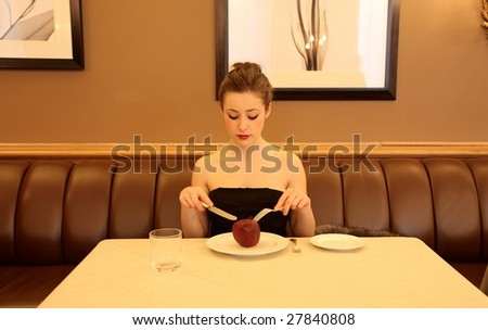 diet concept: woman eating an apple in a restaurant - stock photo