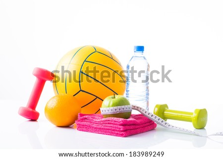 Diet diabetes weight loss concept with ball, tape measure, organic green apple, pink and green dumbbels, towels and natural bottle of sparkling water on a white background.  - stock photo