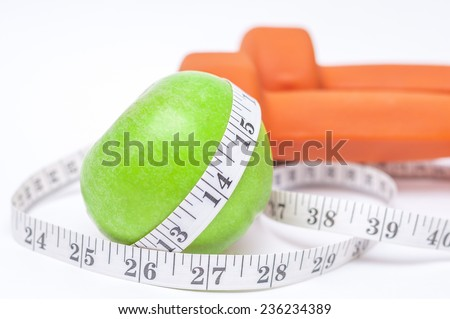 Diet diabetes weight loss concept with tape measure organic green apple and yellow dumbbels on a white background - stock photo