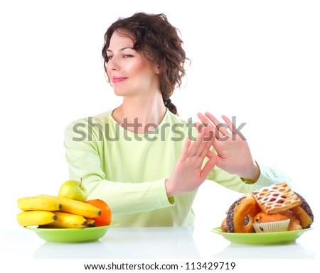 Diet. Dieting concept. Healthy Food. Beautiful Young Woman choosing between Fruits and Sweets. Isolated on white - stock photo