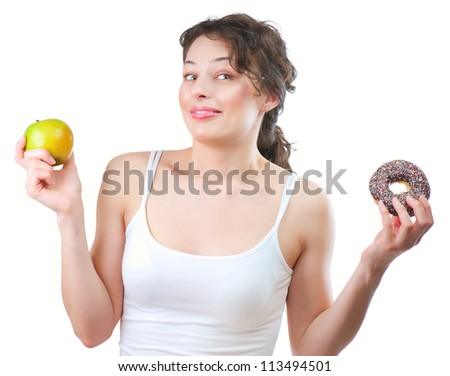 Diet. Dieting concept. Healthy Food. Beautiful Young Woman choosing between Healthy and Unhealthy Food.Fruits or Sweets. Isolated on a White Background - stock photo