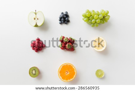 diet, eco food, healthy eating and objects concept - ripe fruits and berries on white surface - stock photo