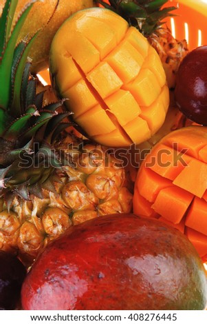 diet food - a lot of fresh raw tropical fruits include pineapple red plum and green mango in orange colander isolated over white background - stock photo
