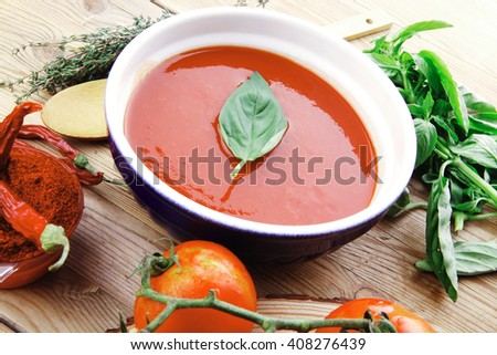diet food : fresh cold tomato soup with basil thyme and dry pepper in big bowl on wood table - stock photo