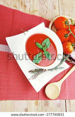 diet food : hot tomato soup with basil thyme and dry pepper in big bowl over red mat on wood table ready to eat