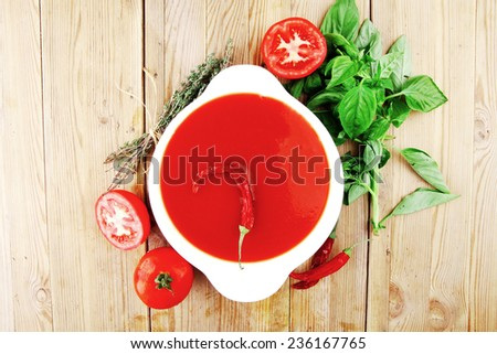 diet food : hot tomato vegetable soup with basil thyme and raw tomatoes in white round bowl over red mat on wood table ready to eat - stock photo