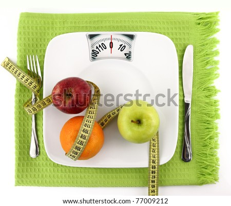 Diet fruit salad on weight scale with measuring tape concept
