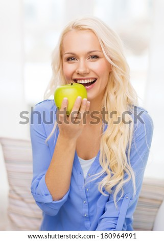 diet, health and home concept - smiling yoing woman with green apple at home - stock photo