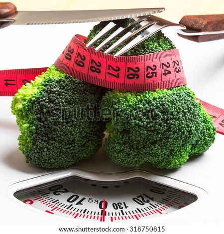 Diet healthy eating weight control concept. Closeup green broccoli measuring tape and fork knife on white scales - stock photo