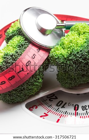Diet healthy eating weight control concept. Closeup green broccoli with measuring tape and stethoscope on white scales - stock photo