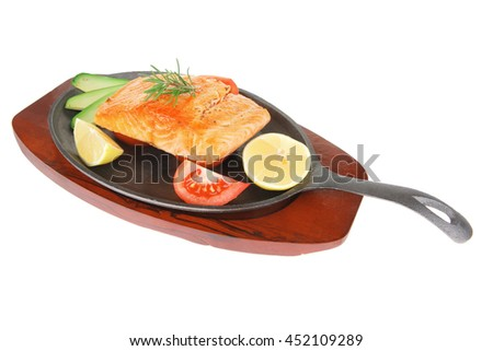 diet healthy food: hot grilled sea salmon fillet served on iron pan over wooden plate isolated on white background - stock photo