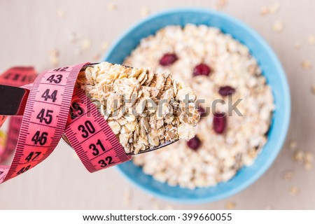 Diet healthy food weight loss concept. Oatmeal in blue bowl and pink measuring tape around spoon on kitchen table, top view - stock photo