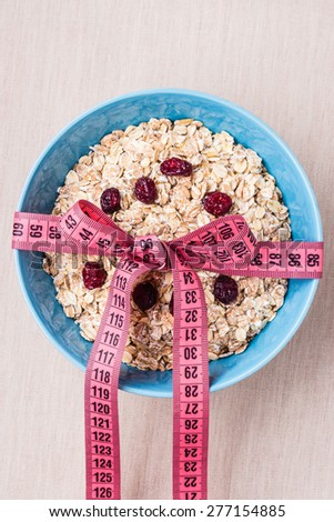 Diet healthy food weight loss concept. Oatmeal in blue bowl with measuring tape around on kitchen table - stock photo