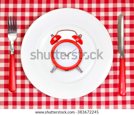 Diet lunch dinner weigh loss time concept.Red alarm clock on round white plate & picnic cloth background.Meal symbol. - stock photo
