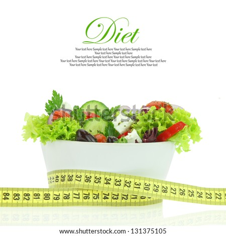 Diet meal. Vegetables salad in a bowl with measuring tape - stock photo