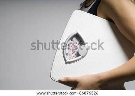 Diet or dieting scale concept held by slim, healthy or trim woman close up - stock photo