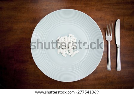 Diet pills on a plate - stock photo