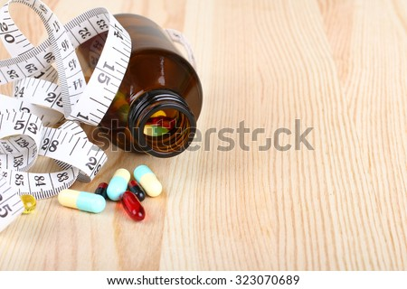 diet pills with measuring tape on wooden background - stock photo