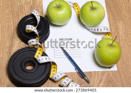 diet plan concept - green apples, measure tape and dumbbell - stock photo