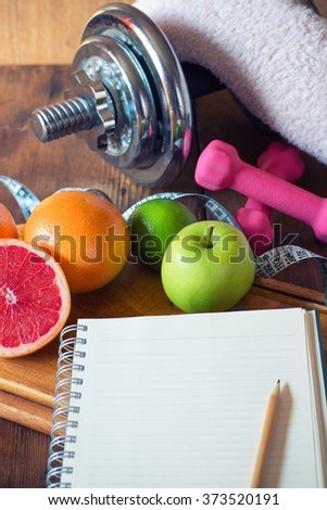 Diet plan. diet plan and a fruits and dumbbells lying on a wooden surface   - stock photo
