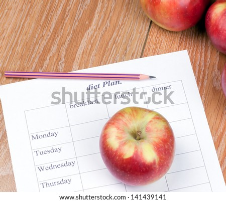 diet Plan. diet plan, pencil and apple lying on a wooden surface - stock photo
