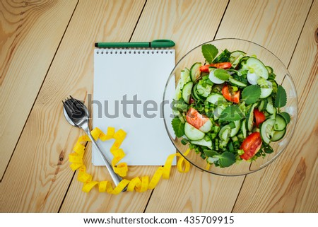 Diet plan, menu or program, tape measure and diet food of fresh salad on wood background, weight loss and detox concept, top view - stock photo