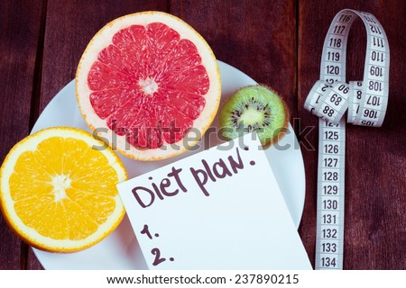 Diet plan. The concept of weight loss, wellness and healthy lifestyle. Vegetarian fruit diet. Products with low fat content. Plate with fruits and measuring tape. - stock photo