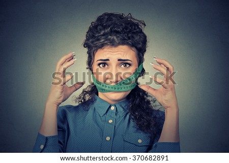 Diet restriction and stress concept. Portrait of young frustrated woman with a green measuring tape around her mouth isolated on gray wall background. Face expression emotion - stock photo