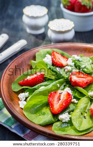 diet salad fresh spinach, strawberries and cheese on black wooden table - stock photo