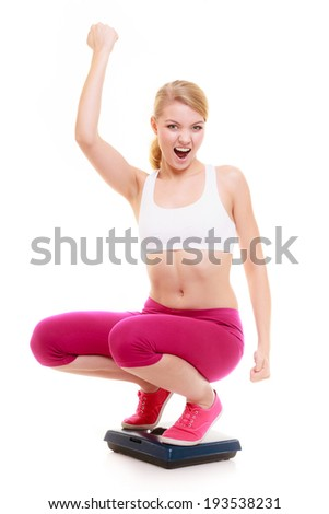 Diet slimming weight loss. Health care and healthy nutrition. Fit girl fitness woman celebrating success on weight scale isolated on white. - stock photo